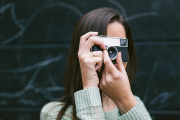 Young woman taking a photo with an old camera.
