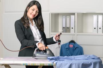 Glückliche Geschäftsfrau bügelt und telefoniert dabei