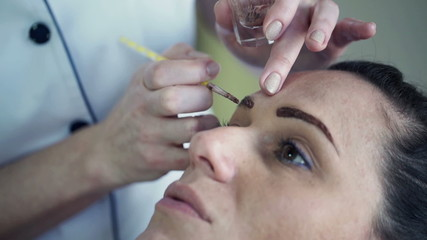 Young woman getting eyebrow makeup at beauty salon