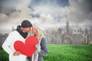 Smiling couple in winter fashion posing with heart shape