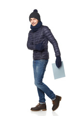 Full length portrait of a young man in winter clothing with empt