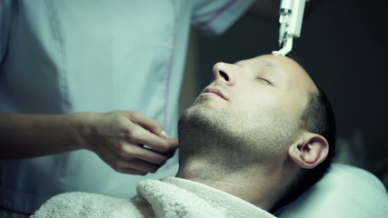 Young man having a botox injection at beauty salon