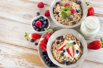 Muesli,  ripe berries and yogurt for healthy  breakfast  on a wo