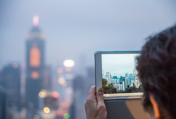 Tourist capturing Hong Kong night skyline with tablet