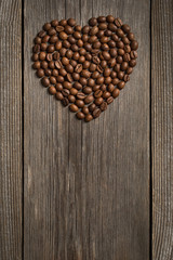 Heart shape made from coffee beans on wooden surface