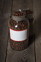 Roasted coffee beans in a cristal jar on wooden table