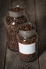 Roasted coffee beans in a cristal jar on wood background