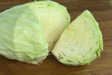 Quarter section of green round cabbage over wooden background