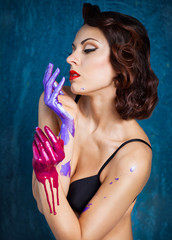 Portrait of a beautiful young woman with colored splashes hands