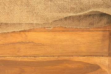 Old sack on top of wooden plank board background