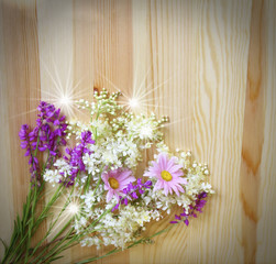 Beautiful wild flowers on wood background, floral arrangement