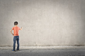 Young boy writing on a blank wall