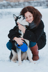 Young woman with husky dog in the winter park