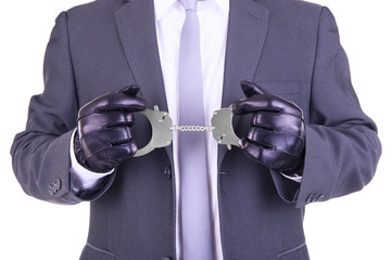 Man in leather gloves holding handcuffs.