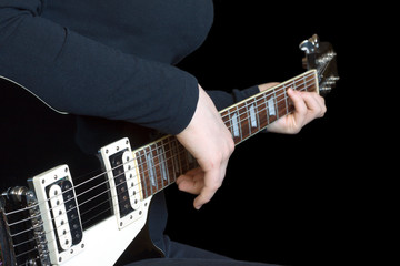 Girl plays on six strings electric guitar isolated on black