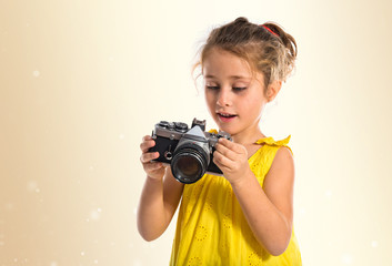 Blonde little girl holding a camera