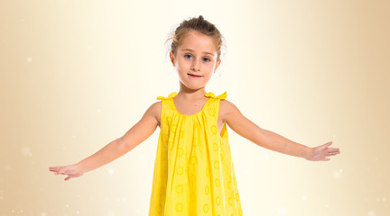 Blonde little girl dancing over white background
