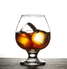 Glass of whiskey with ice on a white background.