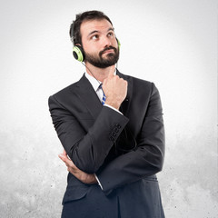 Young businessman listening music over white background
