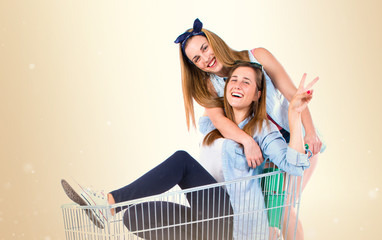 Girls playing with supermarket cart over white background