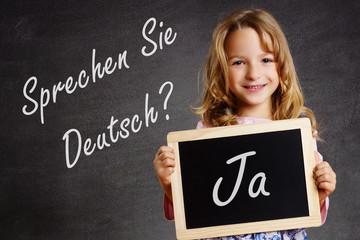 Sprechen Sie Deutsch? Kind hält Tafel