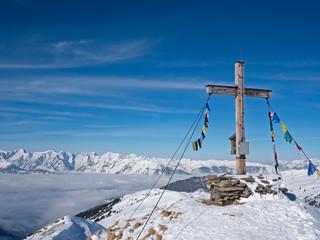 Gipfelkreuz vor Alpenlandschaft