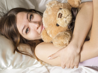 Girl lying in the bed with a soft toy