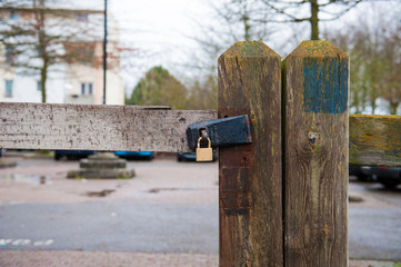 Wood gate closed with pad lock, fence with texture