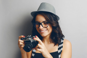 Beautiful girl in a hat with camera.