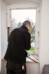 Carpenter removing an old window