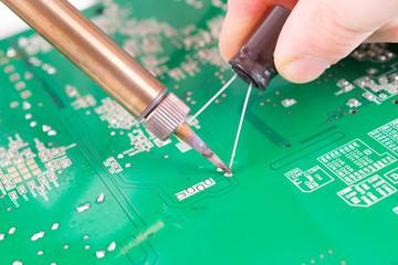 Serviceman soldering on PCB