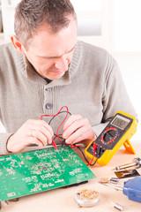 Serviceman checks PCB with a digital multimeter