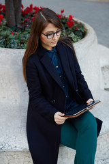 Businesswoman in glasses working outdoors with digital tablet pc