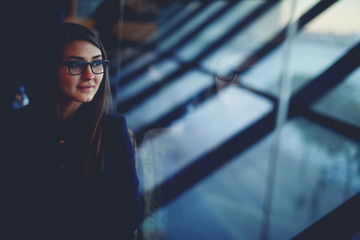 Charming woman in glasses looking out in big window