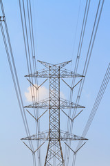 High tension electrical tower against blue sky