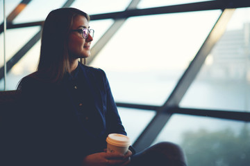Attractive woman looking out in big window while in airport hall