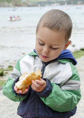 Child eating fish outdoors