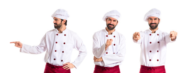 Chef pointing to the front over white background