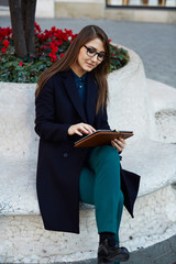 Freelancer girl using tablet pc sitting on bench outdoors