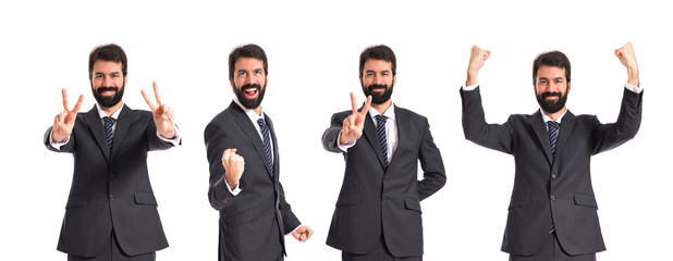 Businessman doing victory gesture over white background