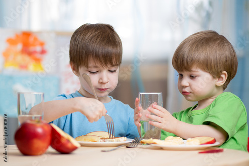 children boys eating healthy food at home - 78011876