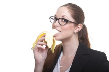 Frau mit Brille beißt von Banane ab