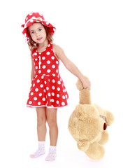 Little girl holding a large paw teddy bear.