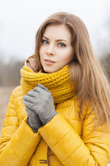 Pretty woman in a yellow knit scarf.  Warm hands.