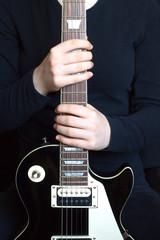 Girl vertical holds black electric guitar neck closeup