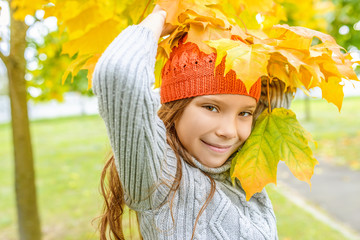 Little girl in sweater with yellow maple leaves