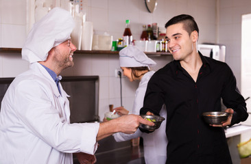 Smiling chefs and waiter working