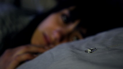 Sad woman in bed at night looking engagement ring