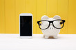 Piggy bank wearing glasses with cellphone - 78019259
