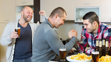 Happy and drunk men armwrestling
